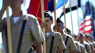 A Joint JROTC Honor Guard prepares to post the colors